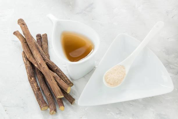 licorice tea, powder and roots on the table - liquirizia foto e immagini stock