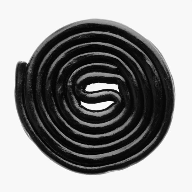 licorice wheel close up on white background - liquirizia foto e immagini stock