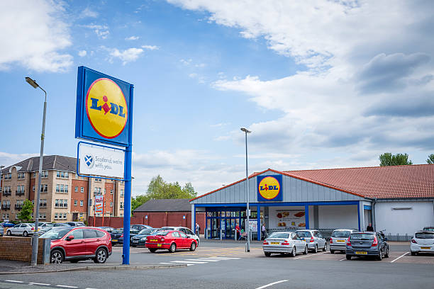 Lidl Supermarket Glasgow, UK - May 30, 2013: Shoppers at the entrance and in the car park of a Lidl supermarket in the Pollockshaws area of Glasgow. theasis stock pictures, royalty-free photos & images