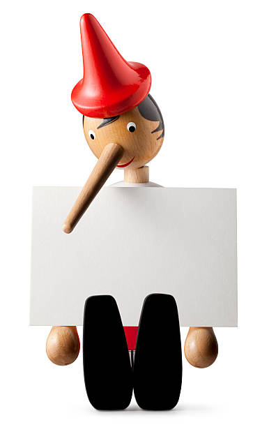 Lie. Pinocchio with a long nose. Pinocchio holding sheet of paper.Similar photographs from my portfolio: pinocchio stock pictures, royalty-free photos & images