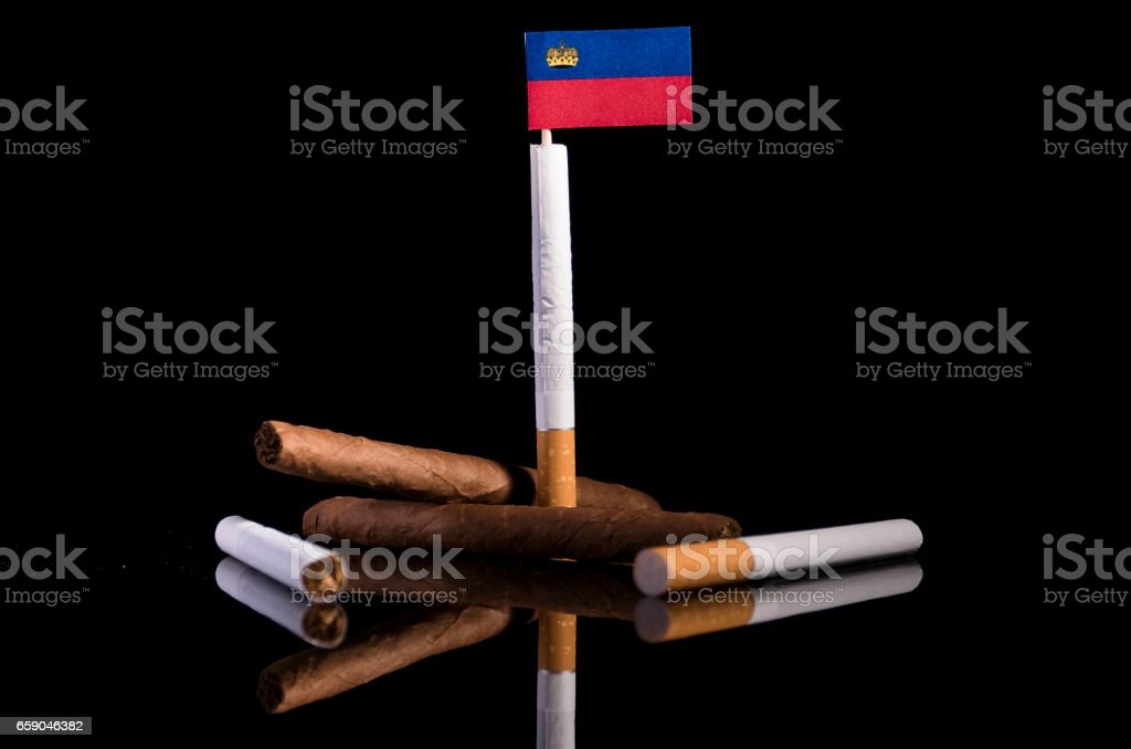 Liechtenstein flag with cigarettes and cigars. Tobacco Industry concept. royalty-free stock photo