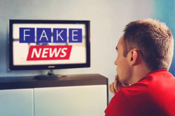 テレビ宣伝の主流メディア偽、偽のニュース レポートの位置しています。ビューアーでは、テレビを見ているし、偽のニュースを信じていません。男は、テレビで嘘を見るように目を閉じる - 不正直 ストックフォトと画像