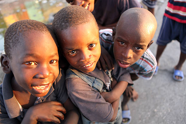 Life after the Earthquake, Haiti Port-Au-Prince, Haiti - February 13th, 2010 : Young Haitian children playing together near an open bazaar street.  haitian ethnicity stock pictures, royalty-free photos & images