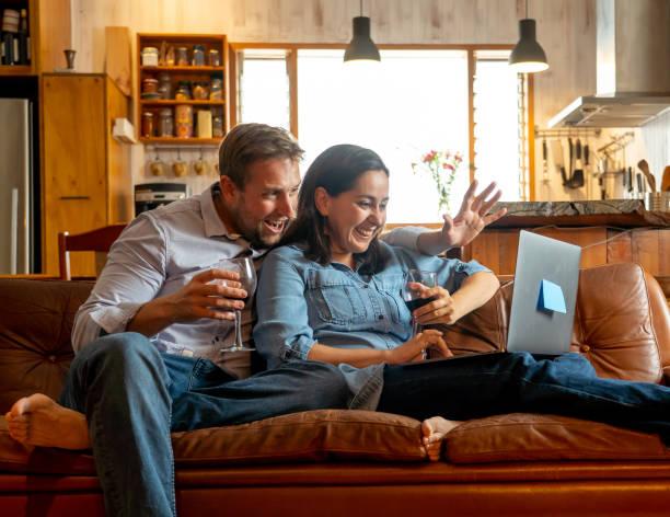 Leben zu Hause Bild von Happy Paar Video ruft Freunde und Familie mit Laptop. Mann und Frau online chatten jubeln mit Wein in virtuelle Feier Party der Lockerung der Coronavirus Einschränkungen. – Foto