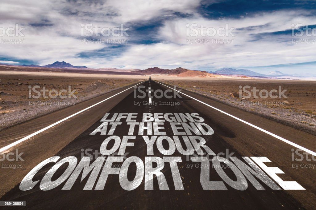 Life Begins at the End of your Comfort Zone written on desert road stock photo