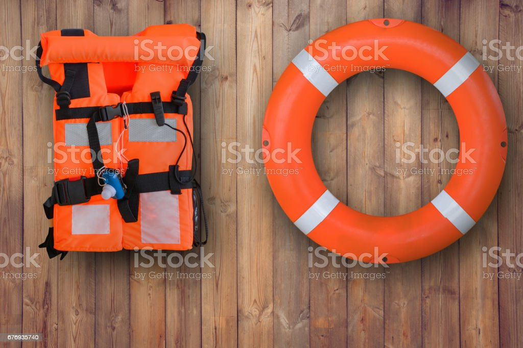 Life buoy and life jacket hanging on wooden wall for emergency response when people sinking to water almost place near pool and beach stock photo