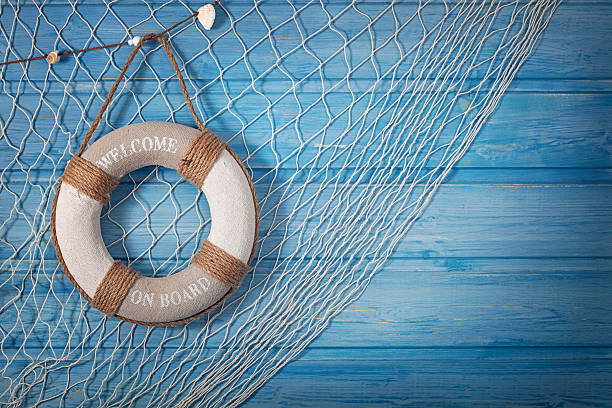 Life buoy and netting on blue background Life buoy decoration on blue shabby background aboard stock pictures, royalty-free photos & images