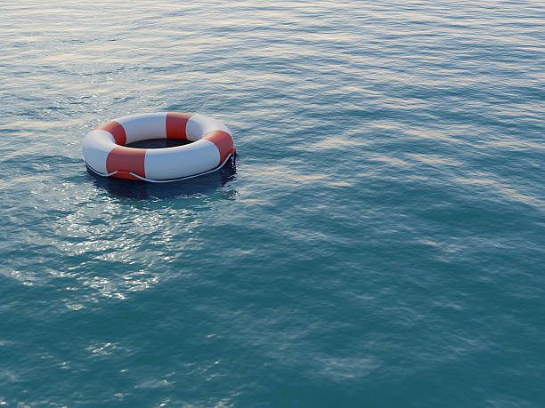 Life buoy floating on a rippled sea A life preserver in open blue water. High resolution 3D render. buoy stock pictures, royalty-free photos & images