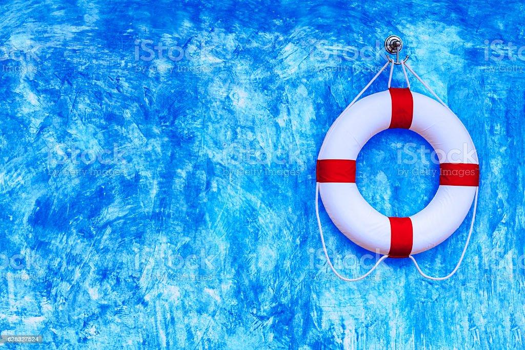 Life buoy hanging on blue polished plaster walls stock photo