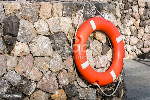 istock Life buoy hanging on stone wall for emergency response when people sinking to water almost place near pool and beach. 1092605566