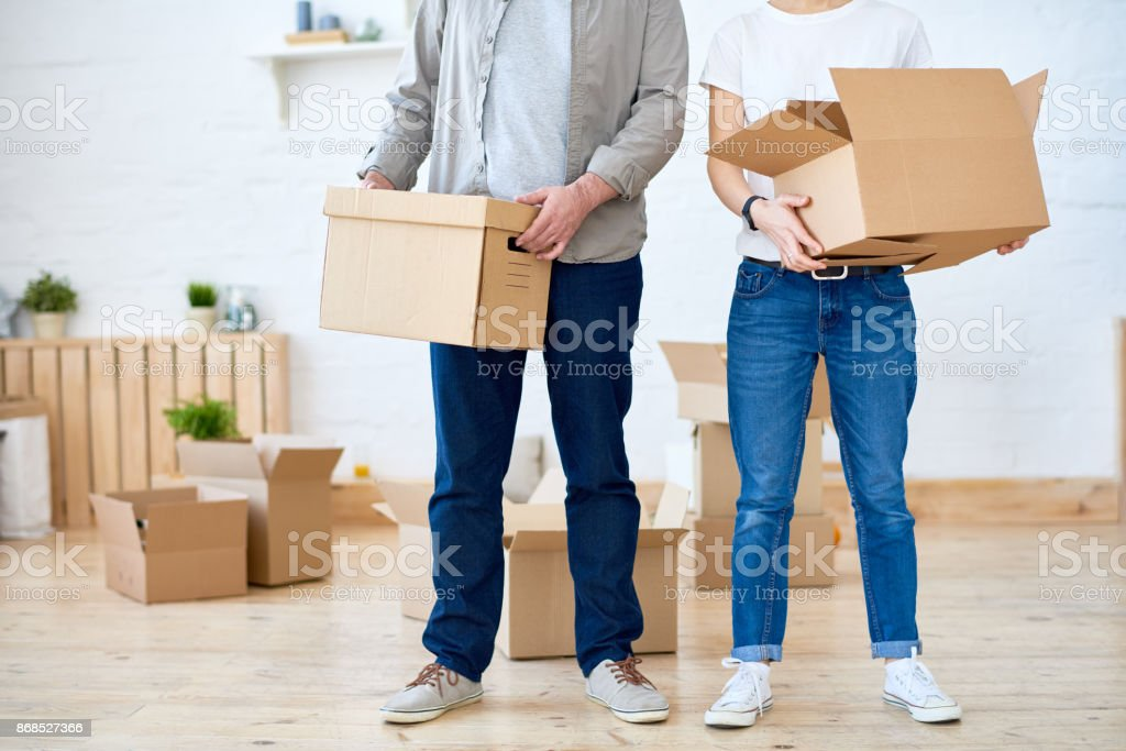 Unrecognizable couple in casual clothing carrying cardboard boxes...