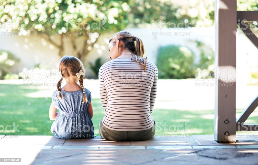 Life doesn't come with a manual, it comes with mom Rearview shot of a young woman and her daughter having a conversation on the porch Adult Stock Photo