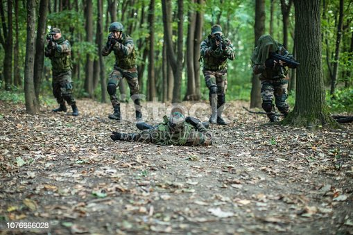 Military Forces Participating War in Natural Environment. One soldier down, lying dead in the middle of forest