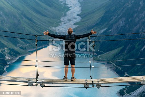 Rear view of Man standing with arms open on rope bridge looking at Mountain landscape. Lonely man enjoying the view from Schlegeis Stausee (Schlegeis Lake) in Tyrol, Austria. Man looking at Schlegeis glacier and beautiful blue lake in the mountains of Tirol, Austria.