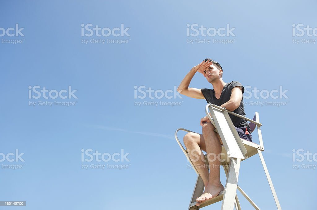 Life gaurd sitting in chair looking into the distance royalty-free stock photo