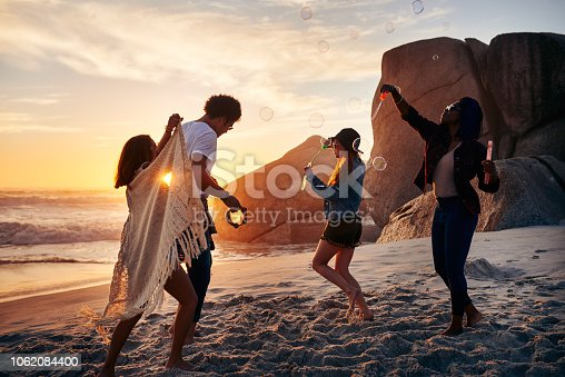 Shot of a group of friends enjoying themselves at the beach