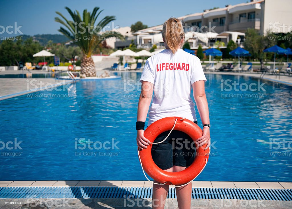 A life guard standing by the pool female lifeguard on duty at a swimming pool Adult Stock Photo