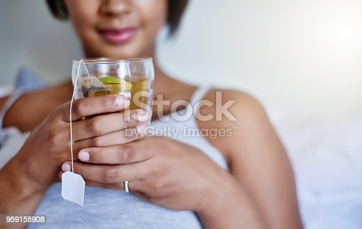 Cropped shot of a young woman relaxing at home with a glass of tea