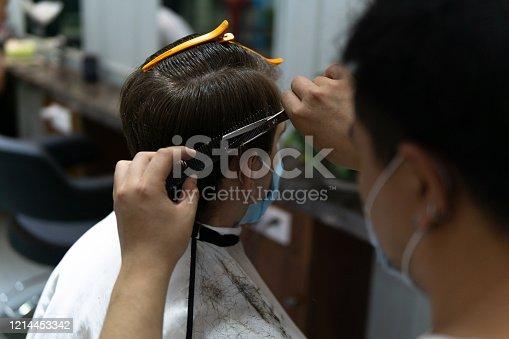 istock Life in Asia under pressure during novel Coronavirus, Covid-19. Caucasian male and Chinese hairdresser wearing medical mask to protect themselves from virus. 1214453342
