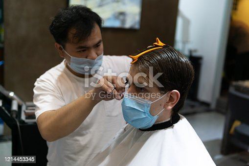 istock Life in Asia under pressure during novel Coronavirus, Covid-19. Caucasian male and Chinese hairdresser wearing medical mask to protect themselves from virus. 1214453345