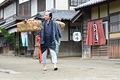 A peasant carrying a heavy load in old Edo.