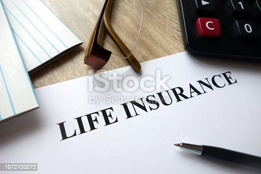 1128824554 istock photo Life insurance document with pen, calculator and glasses on desk 1072120272