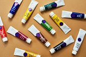 Studio shot of a various coloured paints against a brown background