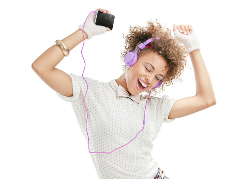 Studio shot of an attractive young woman listening to music on her phone against a white background