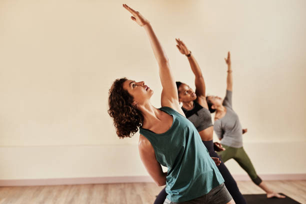 Life is all about balance Shot of a group of young men and women practicing yoga in a fitness class yoga studio stock pictures, royalty-free photos & images