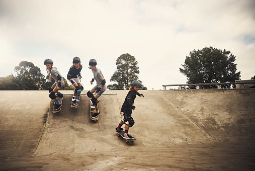 Shot of a group of young girls skateboarding together at a skatepark