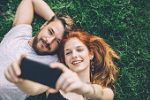 Young couple laying on green grass . Taking selfie with smart phone. They are happy and joyful. Enjoying in summer day.