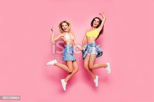 istock Life is cool! Beautiful attractive funny joyful cheerful relaxed carefree girls clothed in casual trendy outfit and white shoes are jumping up ans holding hands, isolated on bright pink background 932236634