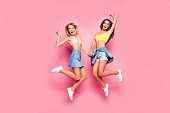 Life is cool! Beautiful attractive funny joyful cheerful relaxed carefree girls clothed in casual trendy outfit and white shoes are jumping up ans holding hands, isolated on bright pink background