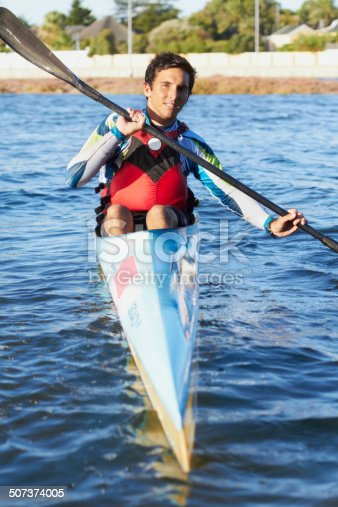 Shot of a young man kayaking in a  river