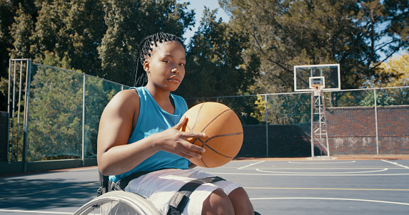 Low angle shot of a young female wheelchair basketball player holding the ball in the center of an outdoor court with the hoop in the background