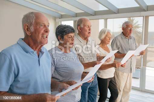 Shot of a group of senior people singing from sheets together in a retirement home