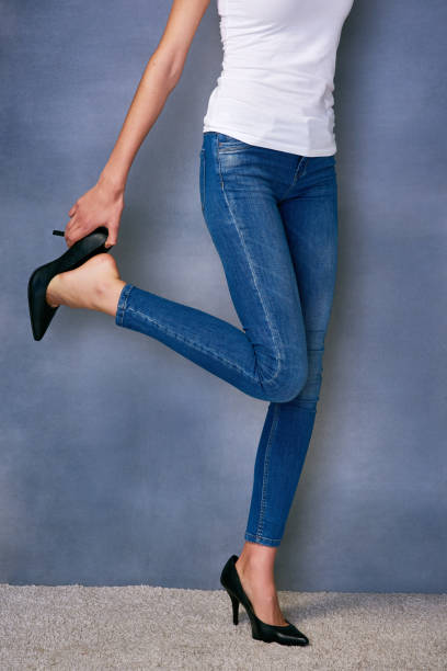 Life is short, heels shouldn't be Shot of an unidentifiable young woman trying on a pair of high heels in studio skinny pants stock pictures, royalty-free photos & images