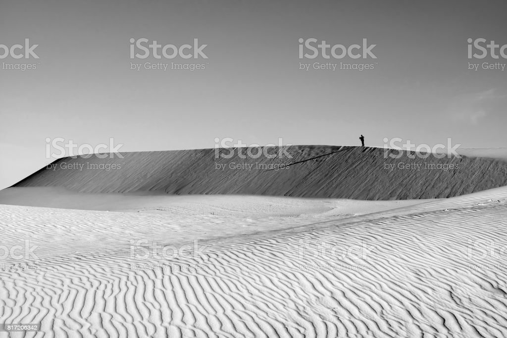 Life is the trip, lonely man on sand hill stock photo