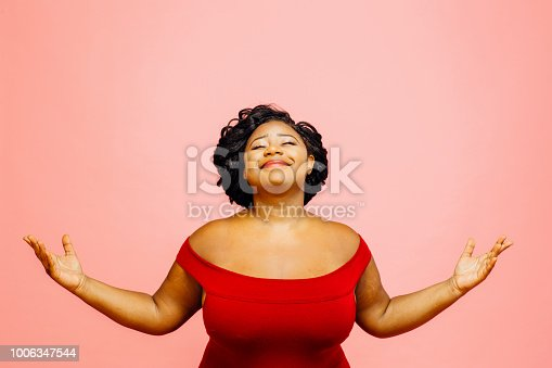Portrait of a confident, satisfied and happy woman with both hands out, isolated on pink