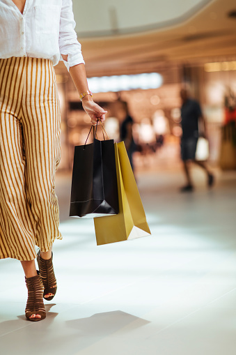 Unrecognisable woman walking through the shopping mall while holding paper shopping bags