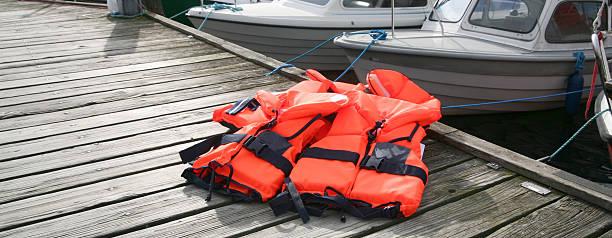 schwimmweste auf deck - wasser sicherheitsausrüstung stock-fotos und bilder