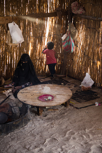 Sahara desert, Egypt - August 22, 2021:Bedouin woman making traditional bread in while child is playing near her.
