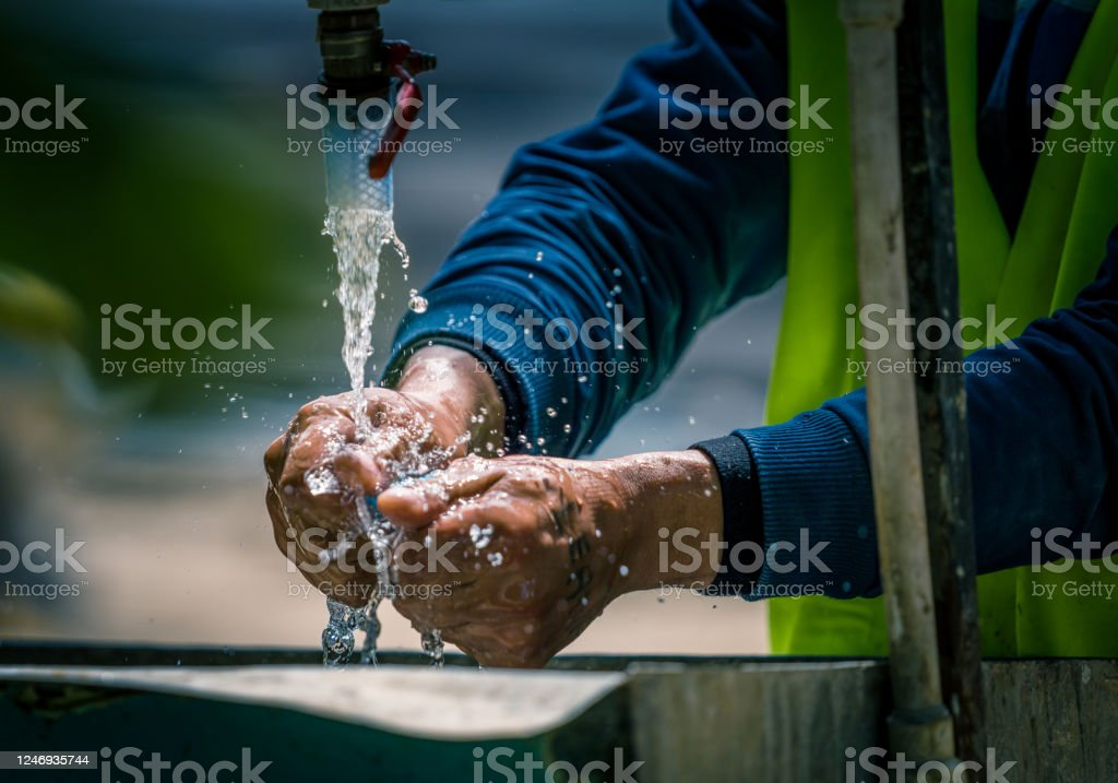 Life on a construction site Workers washing their hands at a makeshift fountain on a construction site Architecture Stock Photo