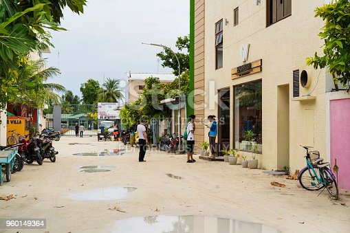 Maafushi Island, Maldives – April 13, 2018: After rain life on street in front of entrance of Maafushi Prison on island Maafushi. Tourists are on street and some people in the prison gate. There are many bikes and bicycles parked on street. This is central atoll, Kaafu Atoll in the Maldives and is around 30 km from capital, of Maldives, Malé.