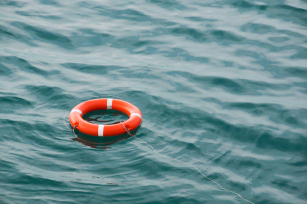 life preserver floating on the sea orange lifebuoy on the waves as the concept of salvation lifeguard stock pictures, royalty-free photos & images