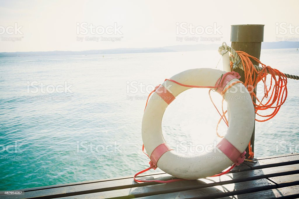 Life preserver on dock overlooking sea water stock photo