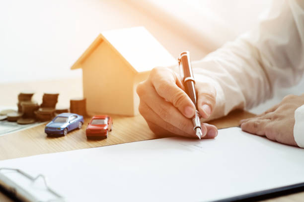 Life protection concept, Businessman or Insurance agent with small house model and Car with contract documents. stock photo