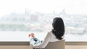 istock Life quality concept with business woman rear view relaxing sitting in rest on cozy armchair in modern hotel guest room or luxury home living room looking toward beautiful city urban scene 1143163414