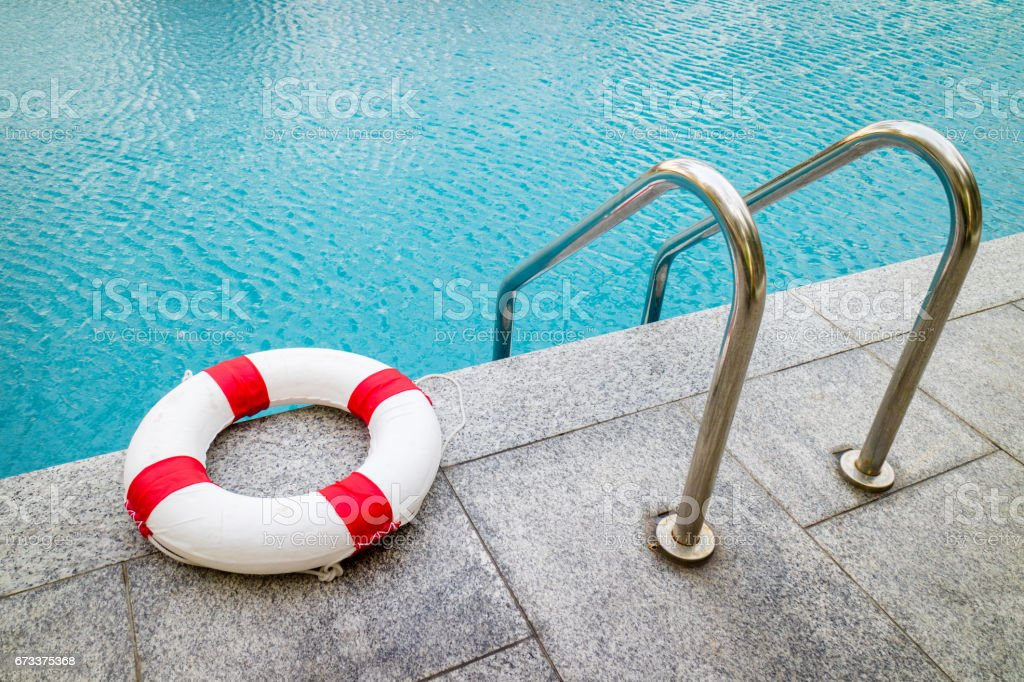 Life ring at swimming pool.emergency tire floating at swimming pool. stock photo