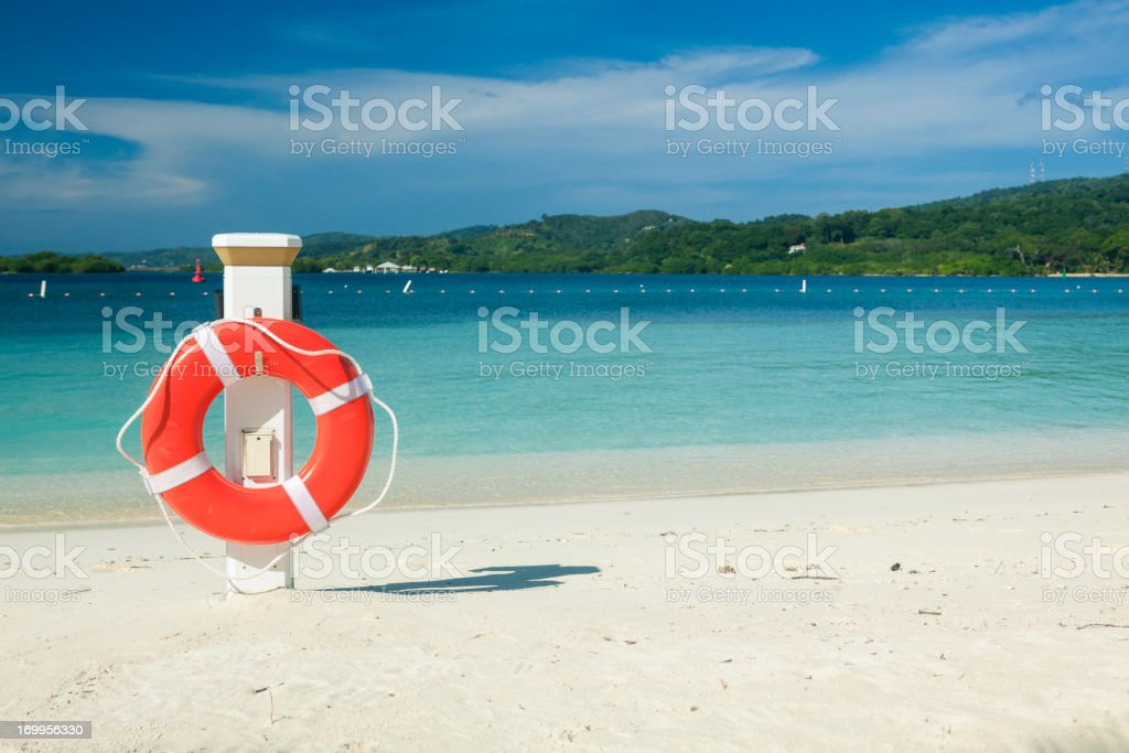 Life ring on tropical beach stock photo